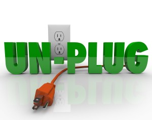 The word Unplug in green letters with an orange electrical cord